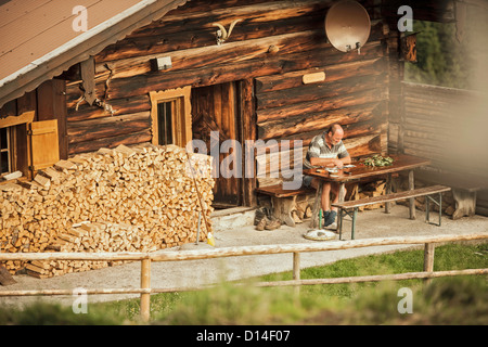 Man reading in porch of log cabin - Stock Photo