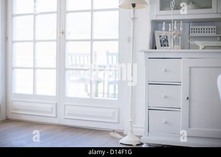White drawers and lamp by windows - Stock Photo