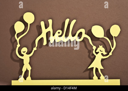 Paper dolls of holding balloons and a hello sign - Stock Photo