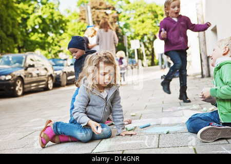Children drawing on sidewalk with chalk - Stock Photo