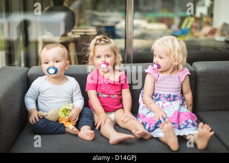 Toddlers sucking on pacifiers together - Stock Photo