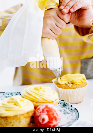 Hands icing cupcake on table - Stock Photo