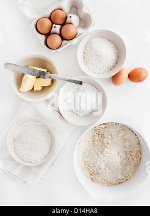 Bowls of sugar, flour, eggs, butter - Stock Photo
