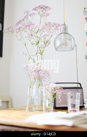 Flowers, radio and water glass on table - Stock Photo