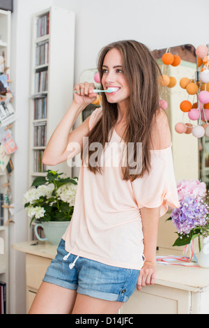 Smiling woman brushing her teeth - Stock Photo