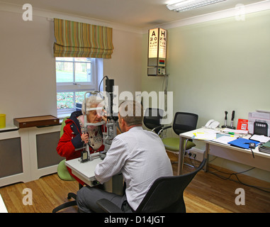 An old woman having her eyes tested for cataracts by a consultant ophthalmologist - Stock Photo