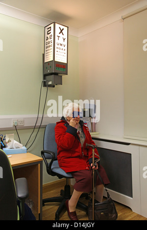 An old woman having her eyes tested for cataracts reading an eye test chart - Stock Photo