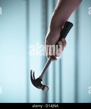 Close up of hand holding hammer - Stock Photo