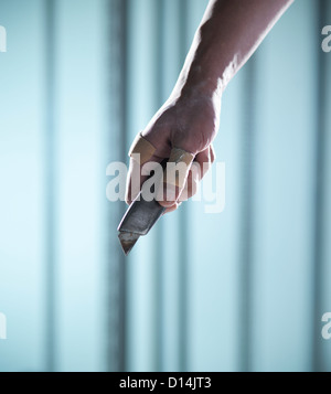 Close up of hand holding box cutter - Stock Photo