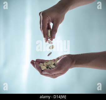 Hands playing with pile of coins - Stock Photo