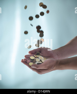 Close up of hands catching pile of coins - Stock Photo