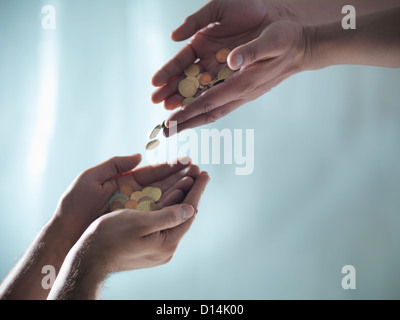 Hands passing pile of coins - Stock Photo