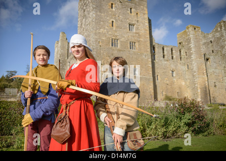 Students in period dress holding weapons - Stock Photo