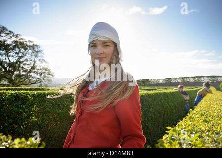Student in period dress in hedge maze - Stock Photo