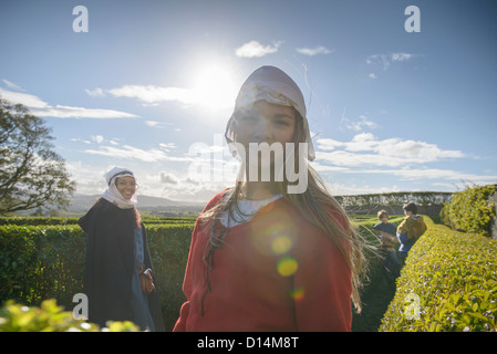 Students in period dress in hedge maze - Stock Photo