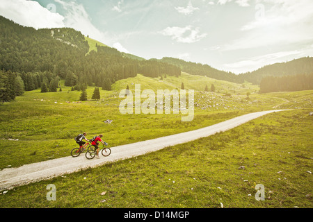 Couple riding bicycles on rural road - Stock Photo