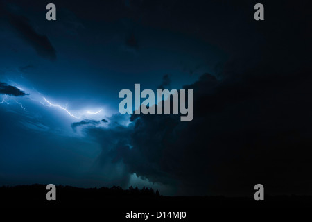 Lighting clouds over rural landscape - Stock Photo