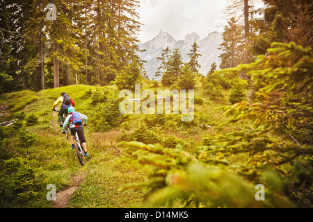 People riding bicycles on dirt path - Stock Photo