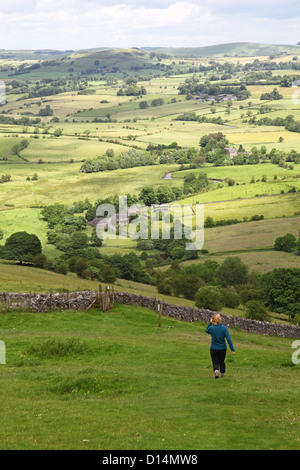 Woman walking through the green fields of the Manifold Valley from Ecton Hill Staffordshire Staffs Peak District - Stock Photo