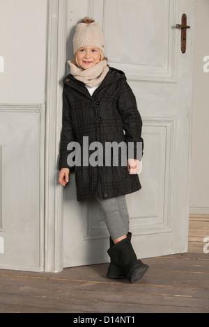 Girl in winter coat and hat indoors - Stock Photo