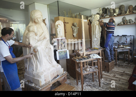 Sculptors chiseling figures from wood - Stock Photo