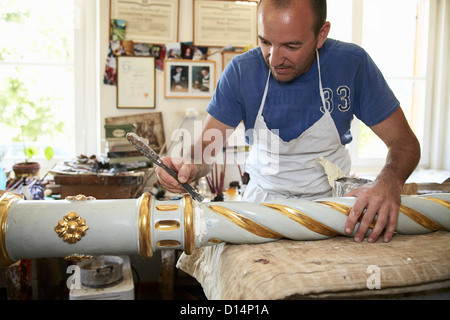 Worker painting carved decorative pole - Stock Photo