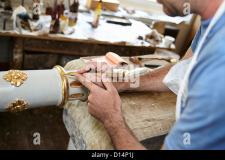 Worker applying gold leaf to pole - Stock Photo