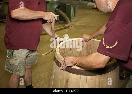 Workers hammering barrel in shop - Stock Photo