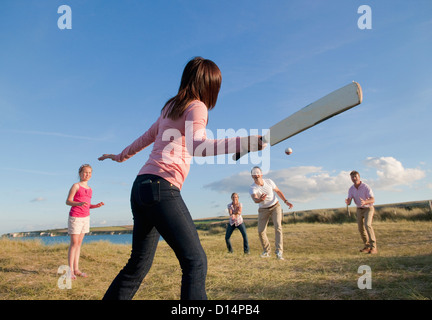Family playing cricket together outdoors - Stock Photo