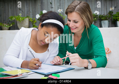Student working with teacher outdoors - Stock Photo