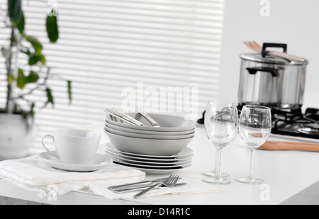 Stacked dishes and cutlery on table - Stock Photo