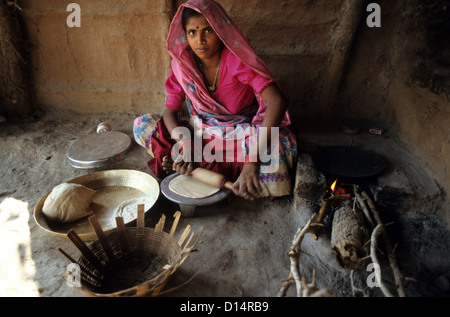 India Madhya Pradesh Kasrawad,  woman prepare indian bread chapathi in kitchen in a village - Stock Photo