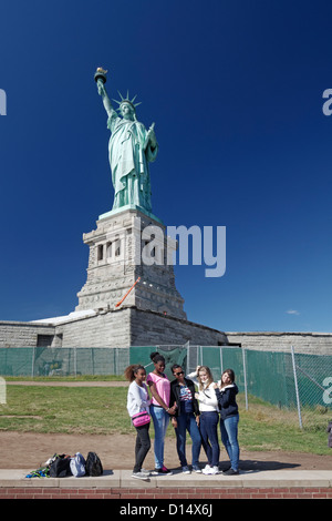 girls posing in front of Statue of Liberty , Liberty Island, New York City - Stock Photo