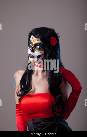 Woman with sugar skull make-up wearing red dress, the Day of the Dead  - Stock Photo