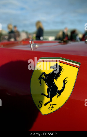A Ferrari badge on the side of a red supercar at a car show. - Stock Photo