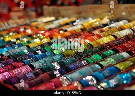 Lines of multi-coloured bracelets at a Christmas market stall Cologne - Stock Photo