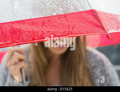 USA, New Jersey, Jersey City, Young woman under umbrella in rain - Stock Photo