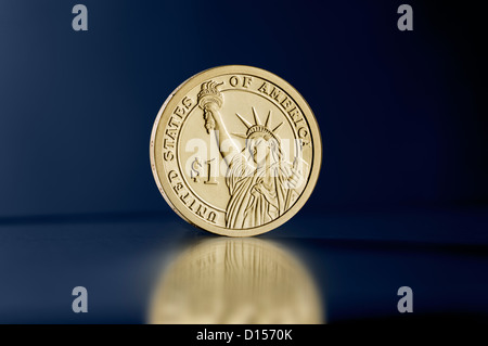 Statue of Liberty one dollar coin upright against blue background - Stock Photo