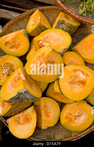 A bamboo basket if filled with quartered wedges of Kabocha Winter Squash for sale at a market in the Philippines. - Stock Photo