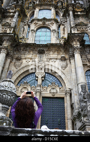 Female tourist taking photo in front of main entrance on west facade of cathedral , Santiago de Compostela, Galicia, - Stock Photo