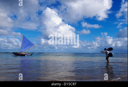 Hawaii, Kauai, Hanalei Bay, Man With Paddle Wading Out Into Water To Sailing Canoe. - Stock Photo