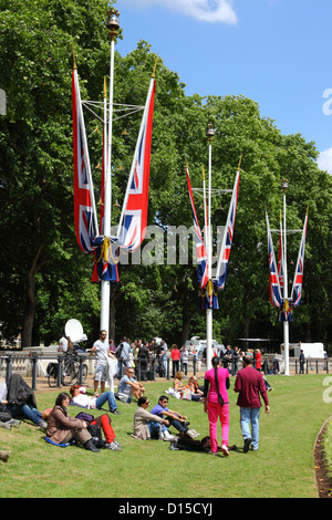 People relaxing on grass next to Victoria Memorial after Trooping the Colour , London , England - Stock Photo
