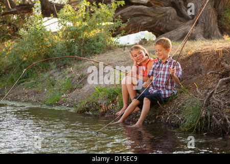 USA, Utah, Lehi, Small boy and girl (6-7) fishing together with makeshift wooden stick in fishing poles in small - Stock Photo