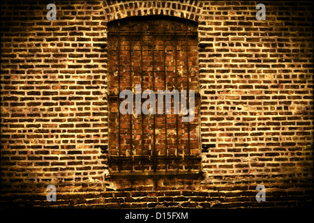 Old grungy brick wall with bars on window background - Stock Photo