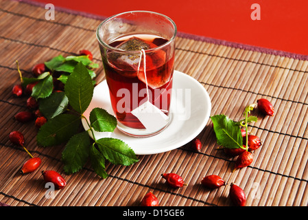 Cup of tea and ripe hip roses (dog rose fruit) on wooden background - Stock Photo