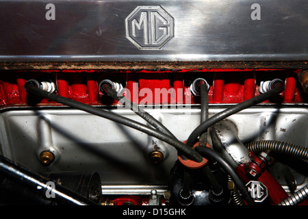 A side view of the chrome MG badge on a classic car engine. - Stock Photo