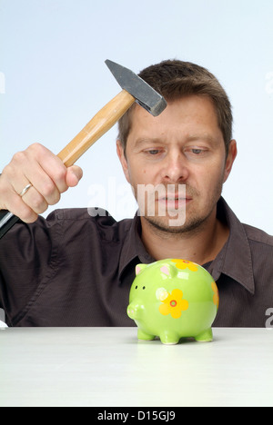Hamburg, Germany, a man slaughters his piggy bank with a hammer - Stock Photo