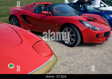 A row of modern and old Lotus cars parked on gravel at a car show. - Stock Photo
