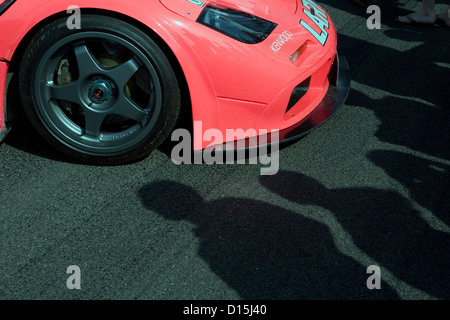 The shadows of people looking at the front of a pink Mclaren F1 racing car at a car show. - Stock Photo