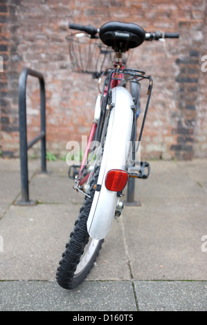 Bicycle with a bucked wheel next to the University of Manchester in Manchester city centre, England - Stock Photo
